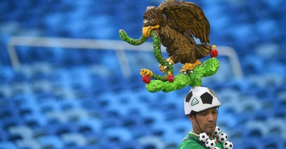Torcedor mexicano carrega símbolo da bandeira nacional na cabeça antes do jogo contra Camarões em Natal