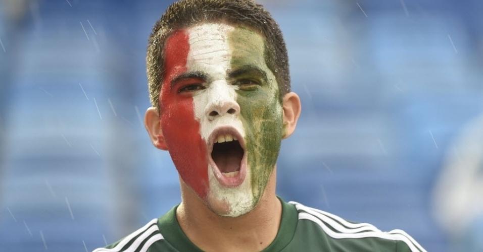 Torcedor mexicano pinta o rosto com as cores da bandeira de seu país antes da partida contra Camarões em Natal, pela Copa do Mundo