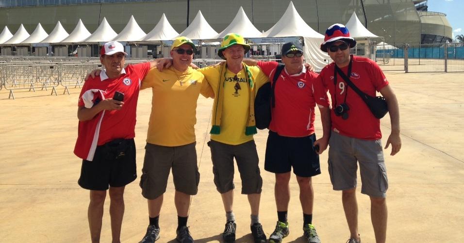 13.jun.2014 - Torcedores chilenos e australianos se abraçam antes de duelo entre as duas seleções pelo grupo B, em Cuiabá