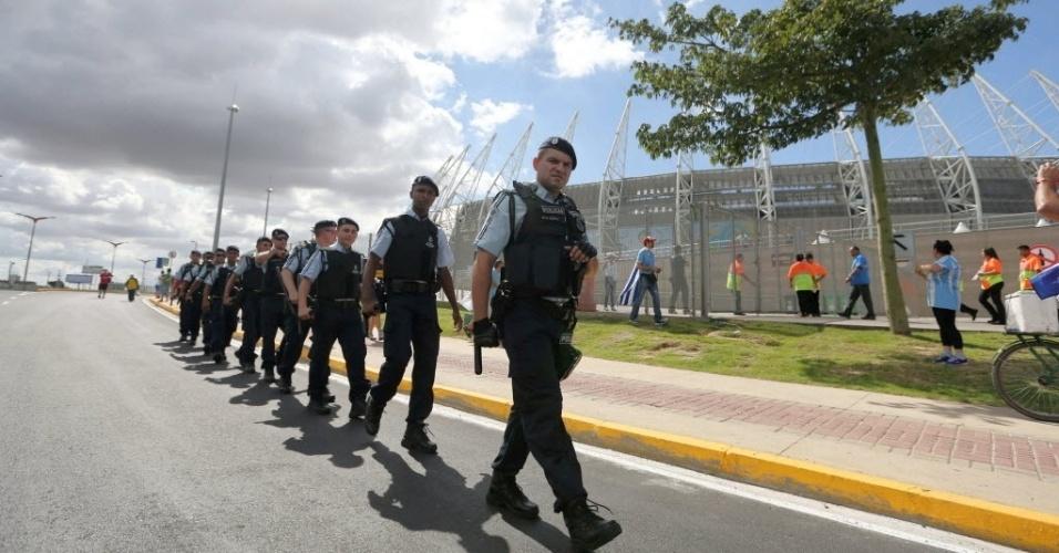 14.06.2014 - Policiais andam em fila em frente ao estádio Castelão