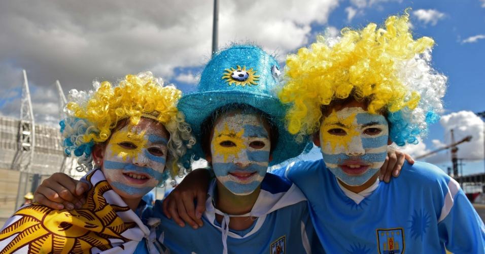 14.06.2014 - Trio de crianças uruguaias pintaram o rosto para torcer por seu país