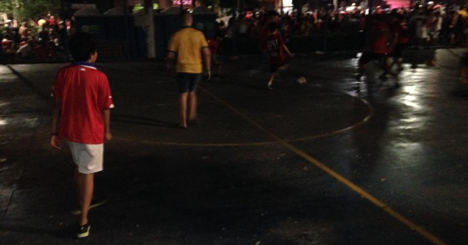 14.jun.2014 - Embalados por música eletrônica, torcedores de Austrália e Chile jogam futebol com bola furada em praça de Cuiabá