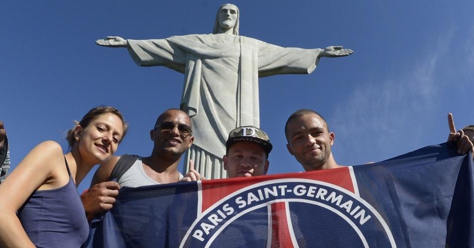 14.jun.2014 - Franceses exibem bandeira do Paris Saint-Germain em visita ao Cristo Redentor, no Rio de Janeiro