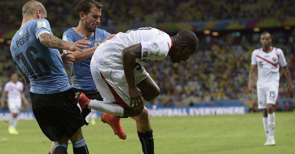 14.jun.2014 - Joel Campbell sofre dura falta de Maxi Pereira durante vitória da Costa Rica sobre o Uruguai