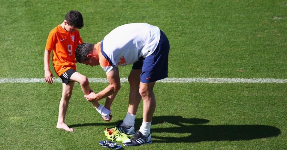 14.jun.2014 - Robin van Persie ajuda o seu filho a trocar as chuteiras durante treinamento descontraído da seleção holandesa