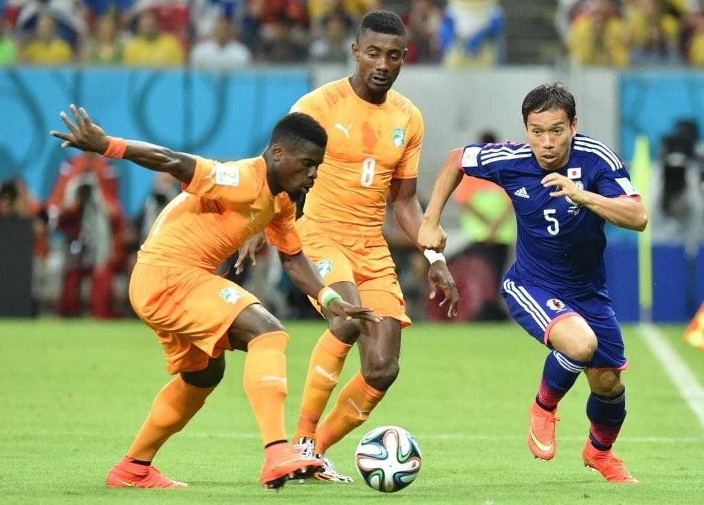 14.jun.2014 - Serge Aurier, da Costa do Marfim, carrega a bola enquanto é observado por Yuto Nagatomo, do Japão
