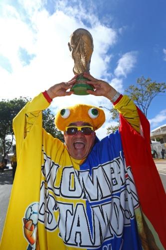 14.jun.2014 - Torcedor colombiano confiante na campanha da seleção nacional ergue réplica da Copa do Mundo na parte externa do estádio Mineirão