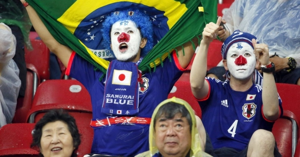14.jun.2014 - Torcedor do Japão com a bandeira do Brasil faz a festa nas arquibancadas da Arena Pernambuco