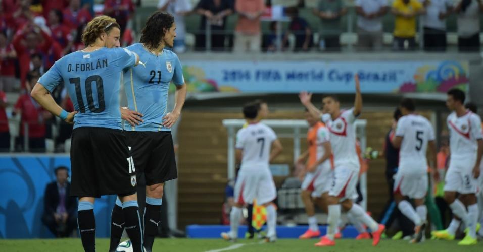 Forlán e Cavani observam a comemoração de Costa Rica enquanto aguardam para reiniciar a partida no Castelão