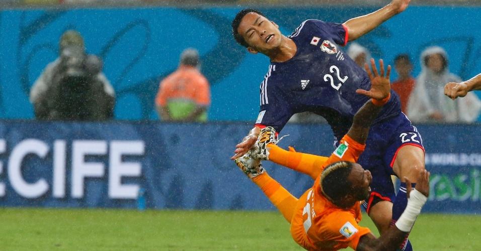 Geoffroy Serey Die e Maya Yoshida vão ao chão após dividida na partida entre Costa do Marfim e Japão