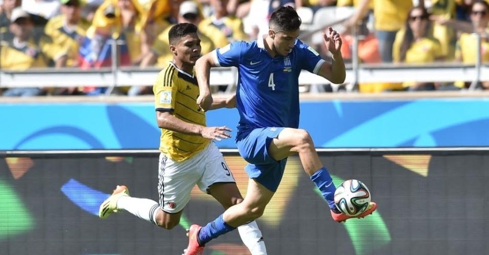 Jogador grego, Konstantinos Manolas, parece voar para escapar de marcação de colombiano durante partida de estreia das equipes na Copa