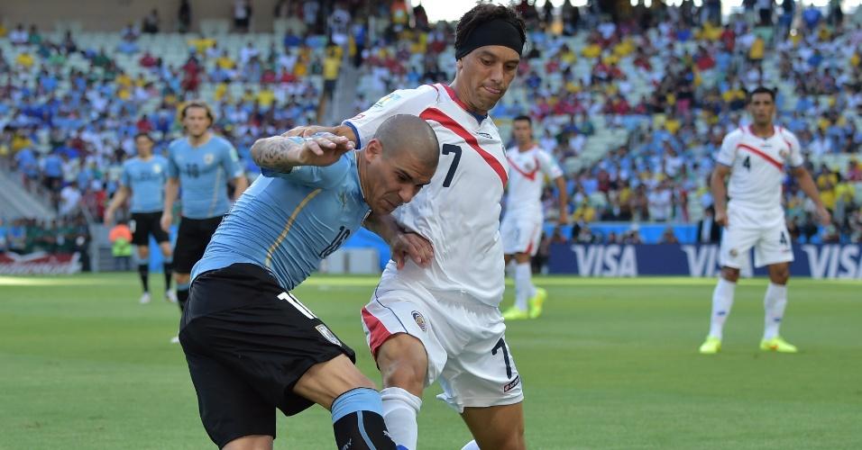 Maximiliano Pereira e Christian Bolanos dividem a bola no jogo entre Uruguai e Costa Rica, no Castelão