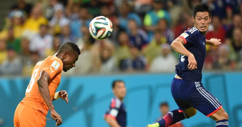 Salomon Kalou, da Costa do Marfim, cabeceia a bola acompanhado de perto pelo japonês Hotaru Yamaguchi
