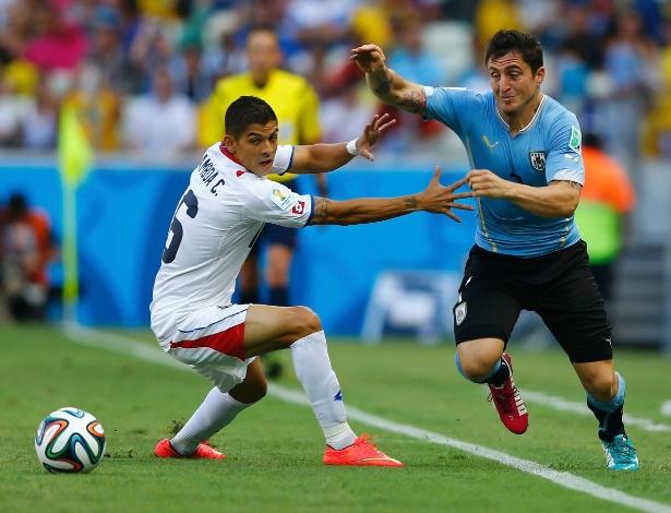 Uruguaio Cristian Rodriguez tenta passar pela marcação de Cristian Gamboa, da Costa Rica, na estreia das seleções na Copa do Mundo