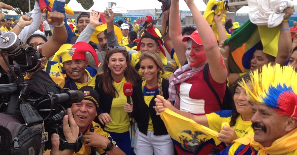 15.jun.2014 - A repórter equatoriana Mariegiselle Carrillo, de 26 anos, entrevista torcedor de seu país horas antes da derrota para a Suiça de virada por 3 a 1 em sua estreia na Copa: torcedores fazem festa