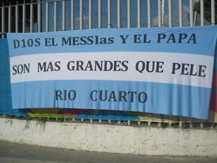 Argentinos estendem faixa destacando Maradona, Messi e o Papa Francisco perto do Maracanã, onde a Argentina estreia contra a Bósnia-Herzegóvina
