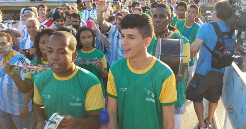Membros de escola de samba acompanham torcida argentina rumo ao estádio Maracanã antes de jogo contra a Bósnia-Herzegóvina