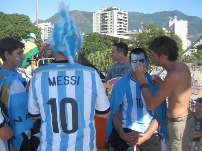 Torcedores argentinos pintam o rosto antes do início do jogo entre Argentina e Bósnia-Herzegóvina, no Maracanã