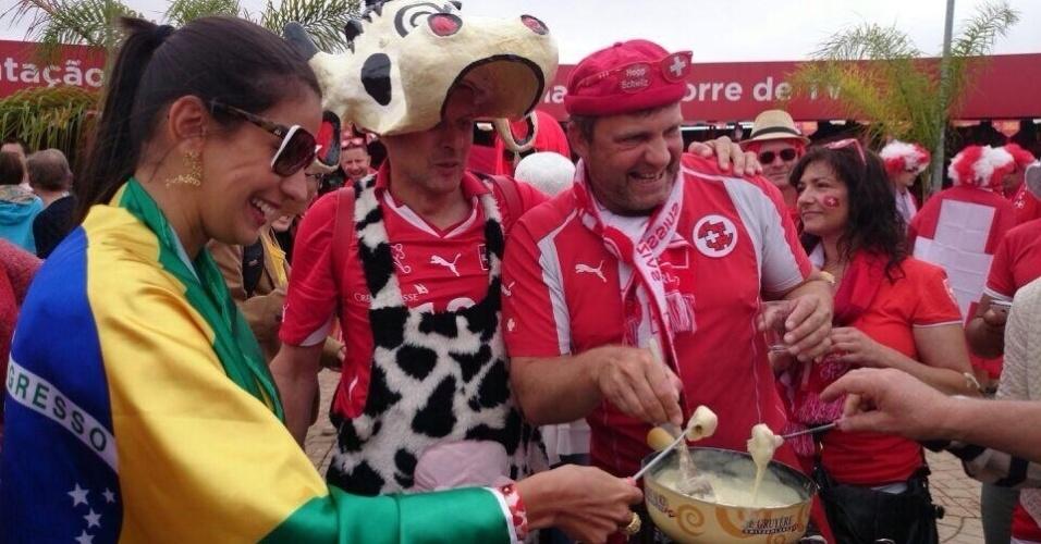 15.jun.2014 - Torcedores suíços ensinam brasileiros a fazer fondue antes da partida contra o Equador em Brasília. Até a 'vaquinha' suíça acompanhou