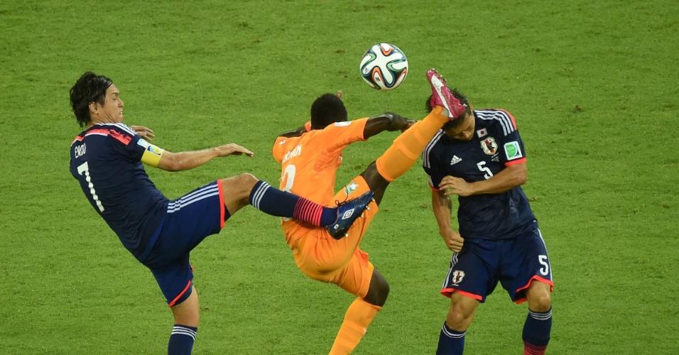 Didier Ya Konan disptua bola com Yasuhito Endo e Yuto Nagatomo