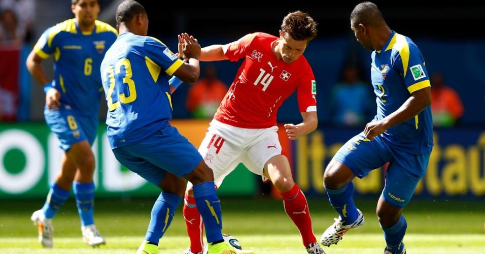 Jogador da Suíça, Valentin Stocker, disputa bola com equatorianos durante partida de estreia das seleções na Copa, em Brasília