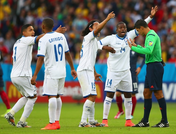 Jogadores de Honduras reclamam com Sandro Meira Ricci após o árbitro brasileiro validar gol da França em que a bola passou por pouco da linha