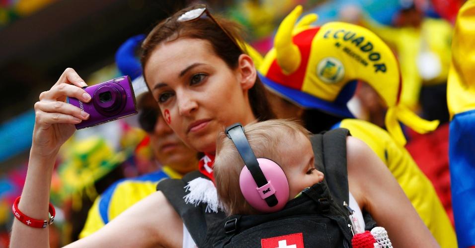 Mãe suíça leva o filhinho dentro de uma espécie de bolsa para assistir à partida contra o Equador