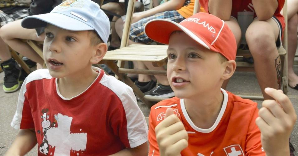 Pequenos suíços assistem à jogo da Suíça contra o Equador em uma praça pública na cidade de Daillens