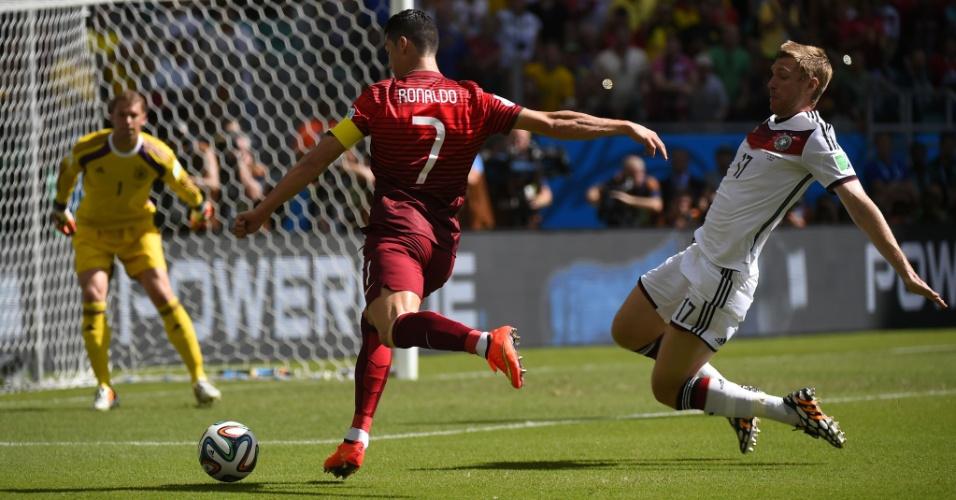16.jun.2014 -  Cristiano Ronaldo faz jogada e tenta a finalização para Portugal enquanto o zagueiro Per Mertesacker, da Alemanha, tenta travar a bola