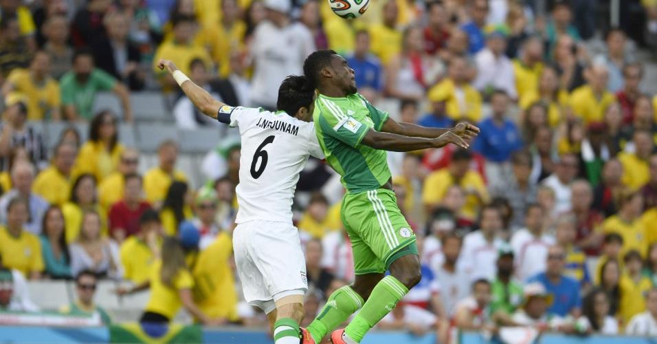 Emenike, da Nigéria, e Nekounam, do Irã, disputam bola pelo alto em partida válida pelo Grupo F