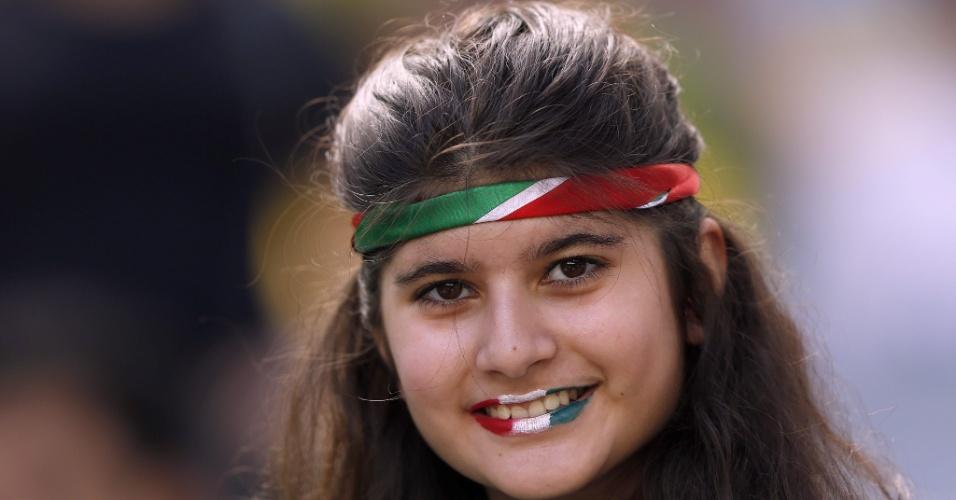 Garota iraniana pinta o rosto com as cores do país asiático na Arena da Baixada