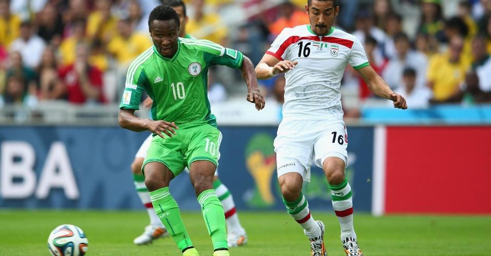 Obi Mikel tenta passe para a Nigéria cercado por jogador iraniano