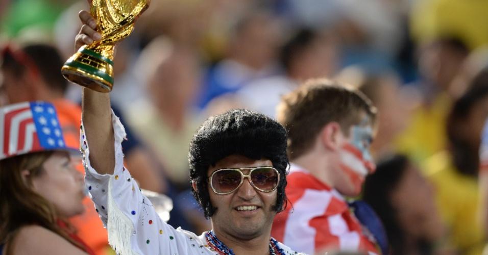 16.jun.2014 - Sósia de Elvis Presley acredita no título dos EUA e carrega réplica da taça da Copa do Mundo na Arena das Dunas
