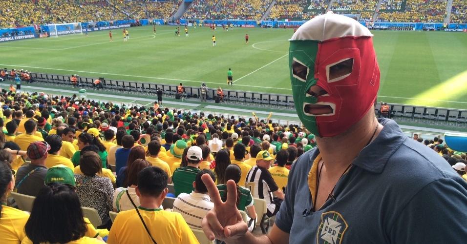 14.jun.2014 - O comediante Marcelo Adnet se escondeu sob uma máscara no meio da torcida do México em Fortaleza