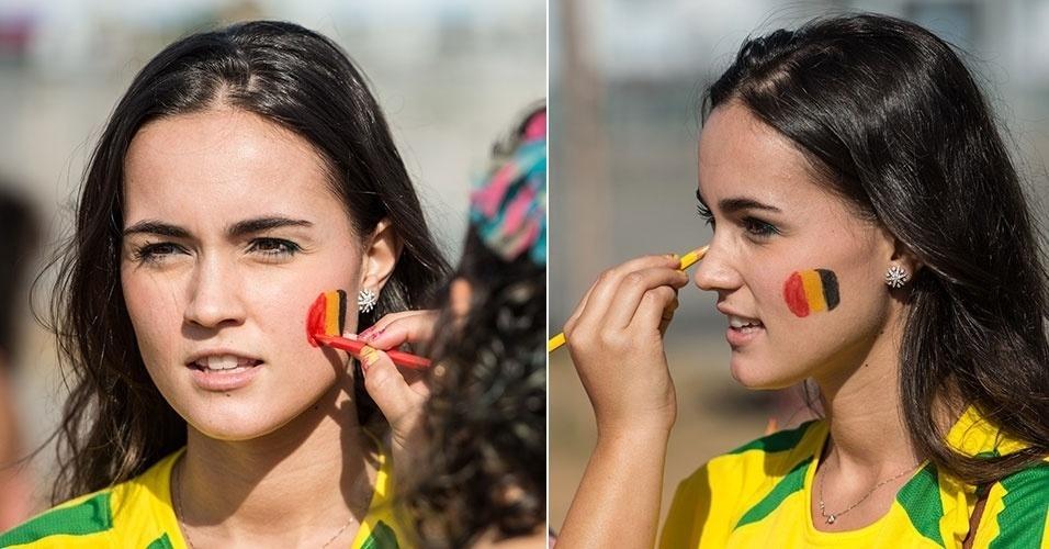 17.jun.2014 - Bela torcedora com a camiseta do Brasil pinta o rosto com as cores da Bélgica para o duelo com a Coreia do Sul no Mineirão