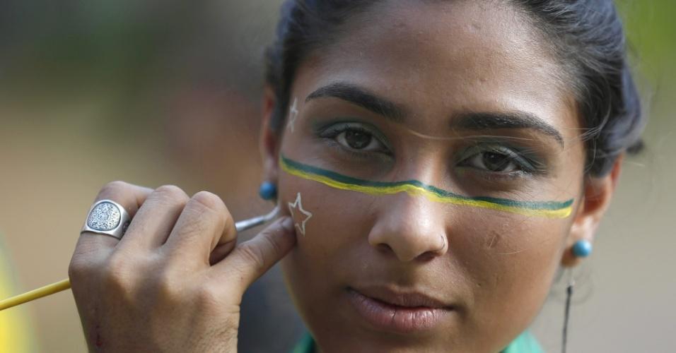 17.jun.2014 - Em São Paulo, torcedora pinta o rosto para o jogo do Brasil contra o México