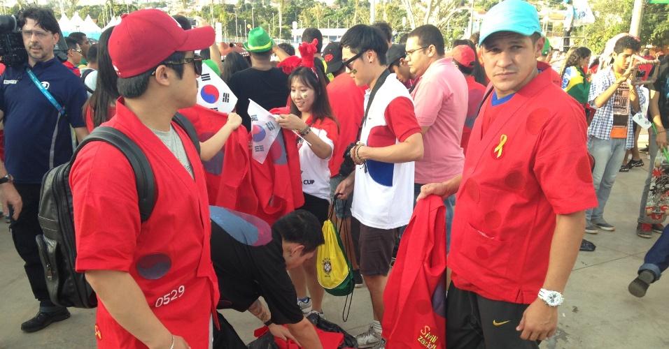 17.jun.2014 - O sul-coreano Kim Mim Kyu (de boné vermelho) e o brasileiro Willian Moura (de boné branco) ajudam a distribuir roupas para aumentar a torcida da Coreia do Sul em jogo da Copa do Mundo, em Cuiabá