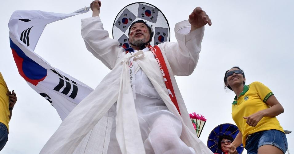17.jun.2014 - Torcedor no lado de fora da Arena Pantanal não economiza nas bandeiras da Coreia do Sul em sua fantasia
