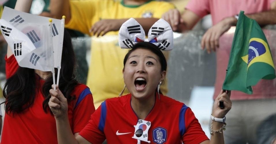 Torcedora vibra com bandeiras sul-coreana e brasileira antes de jogo entre Rússia e Coreia do Sul