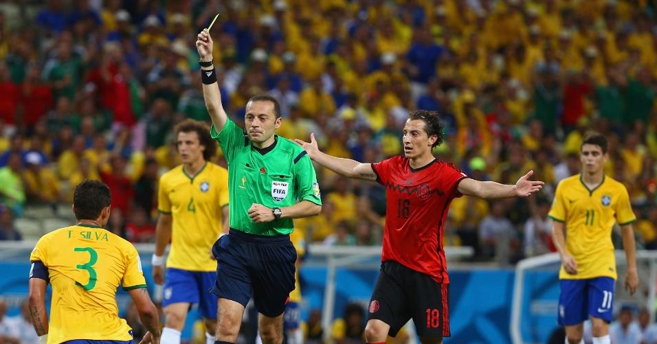 17.jun.2014 - Árbitro Cuneyt Cakir mostra o cartão amarelo para Thiago Silva após o zagueiro cometer falta na entrada da área