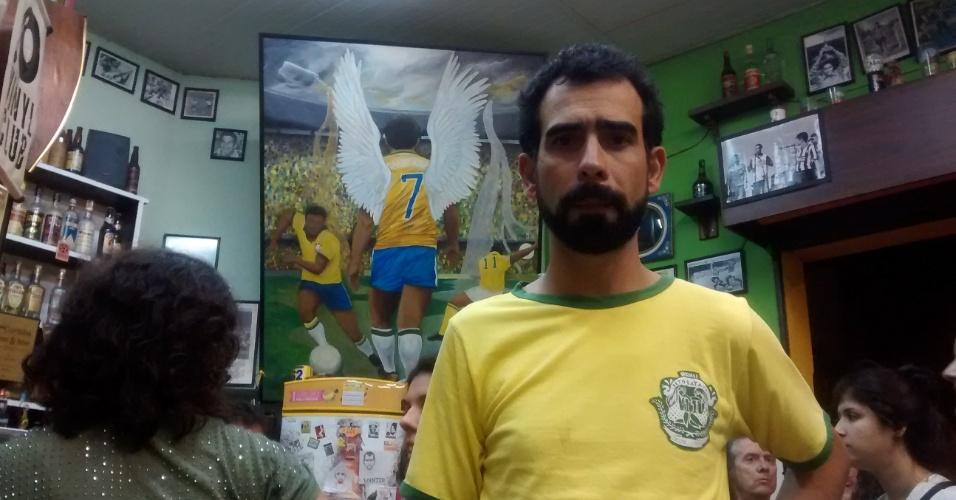 Arlindo Ventura, o Magrão, posa diante de quadro do Anjo das Pernas Tortas