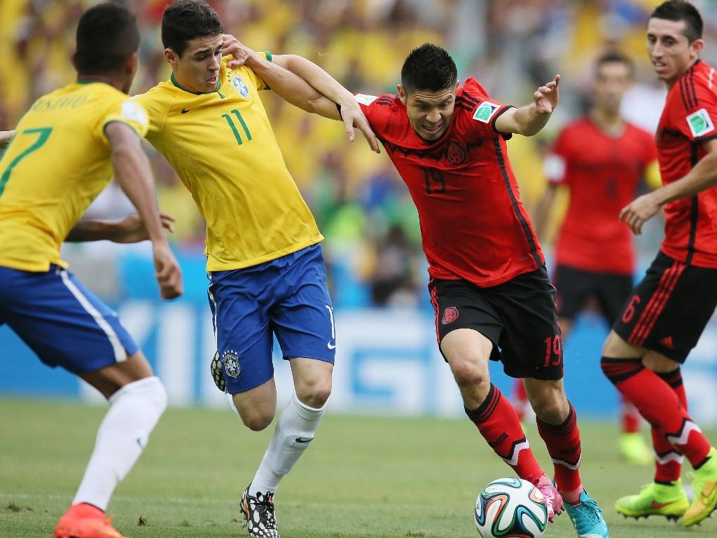 17.jun.2014 - Brasileiro Oscar marca de perto o mexicano Peralta durante a segunda partida das seleções no Mundial