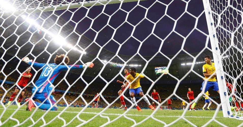 17.jun.2014 - Brasileiros e mexicanos observam a bola após Ochoa fazer grande defesa em finalização de Thiago Silva