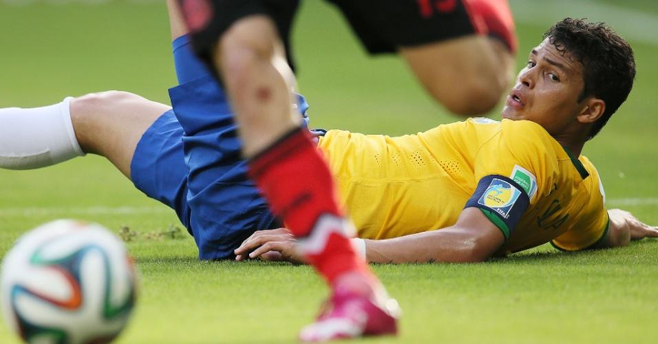 17.jun.2014 - Caído no gramado, Thiago Silva observa o mexicano Oribe Peralta sair jogando com a bola dominada no Castelão