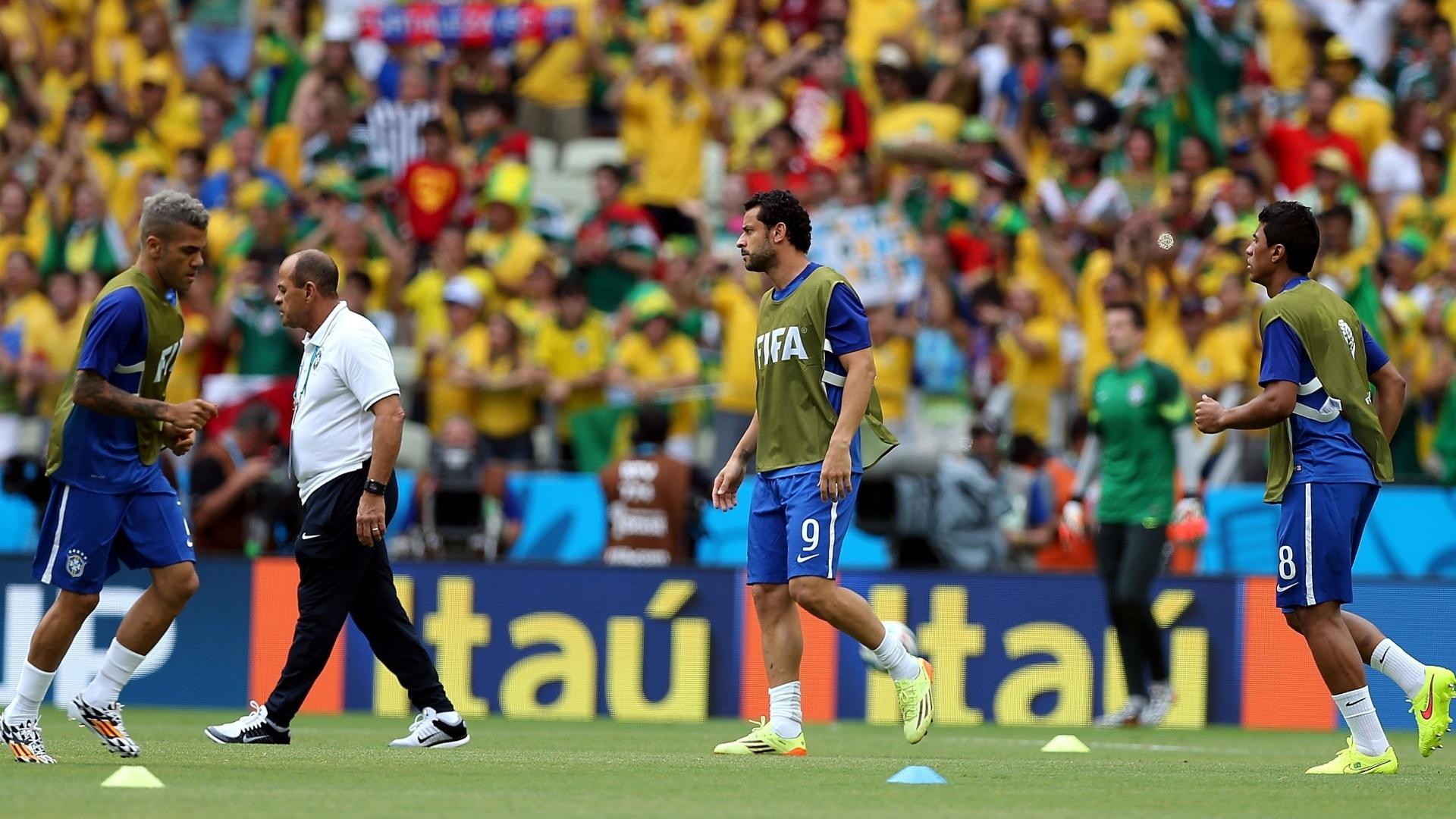 17.jun.2014 - Daniel Alves, Fred e Paulinho fazem aquecimento no gramado do Castelão
