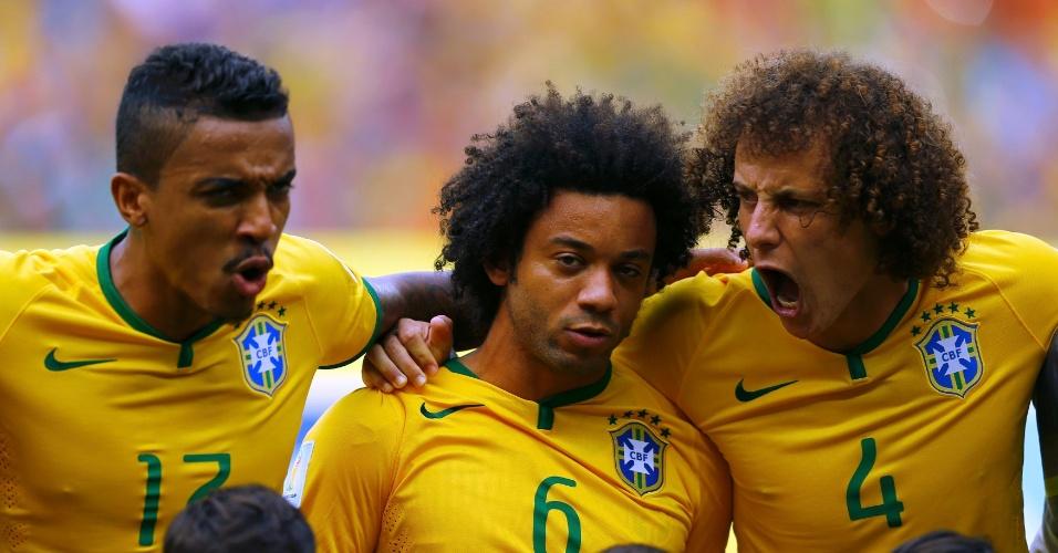 17.jun.2014 - David Luiz, Luiz Gustavo e Marcelo cantam o hino nacional antes da partida contra o México