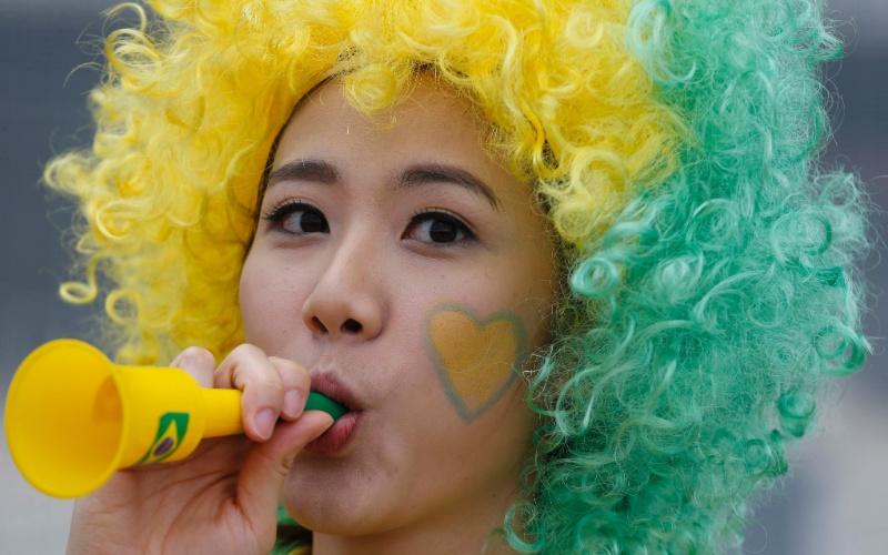 De peruca e cara pintada, torcedora do Brasil faz barulho horas antes do duelo com o México