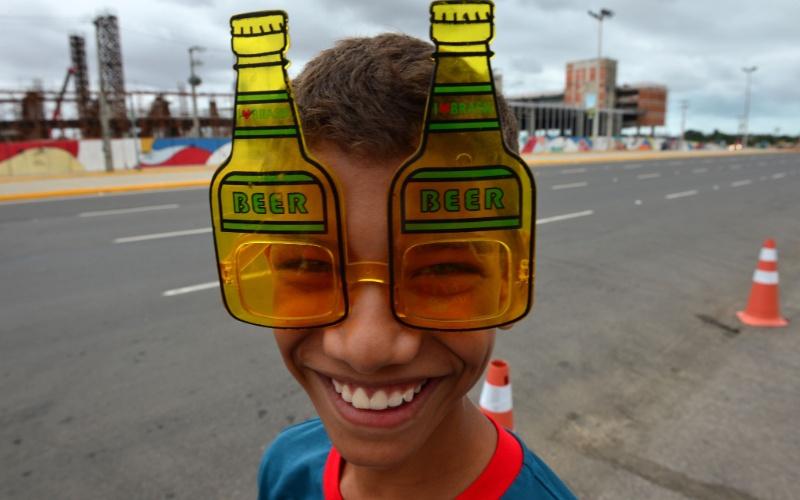 Garoto usa óculos em formato de garrafas de cerveja na chegada ao Castelão