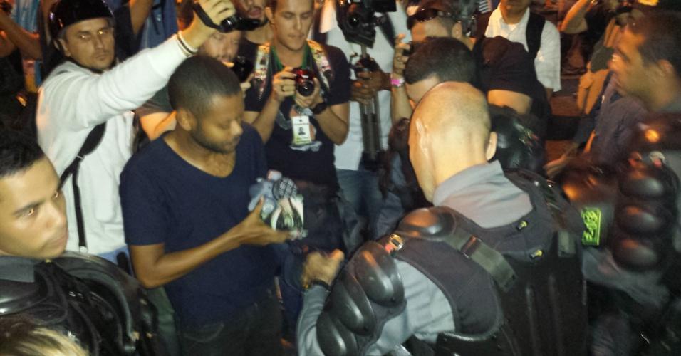 Homem tem material revistado por policial em ato em Copacabana, no Rio de Janeiro