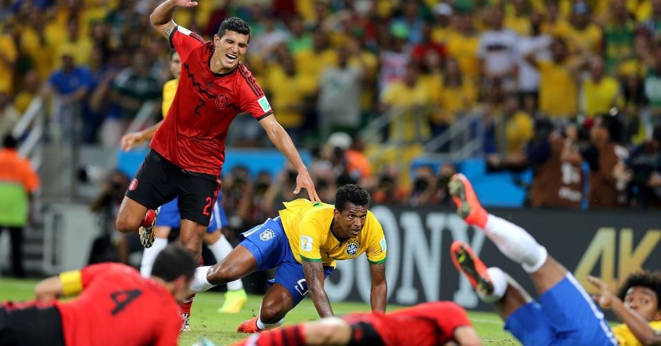 17.jun.2014 - Jogadores de Brasil e México ficam caídos no gramado enquanto Jô observa a bola ir para fora